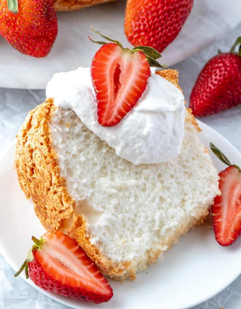 Slice of angel food cake with whipped cream and strawberries