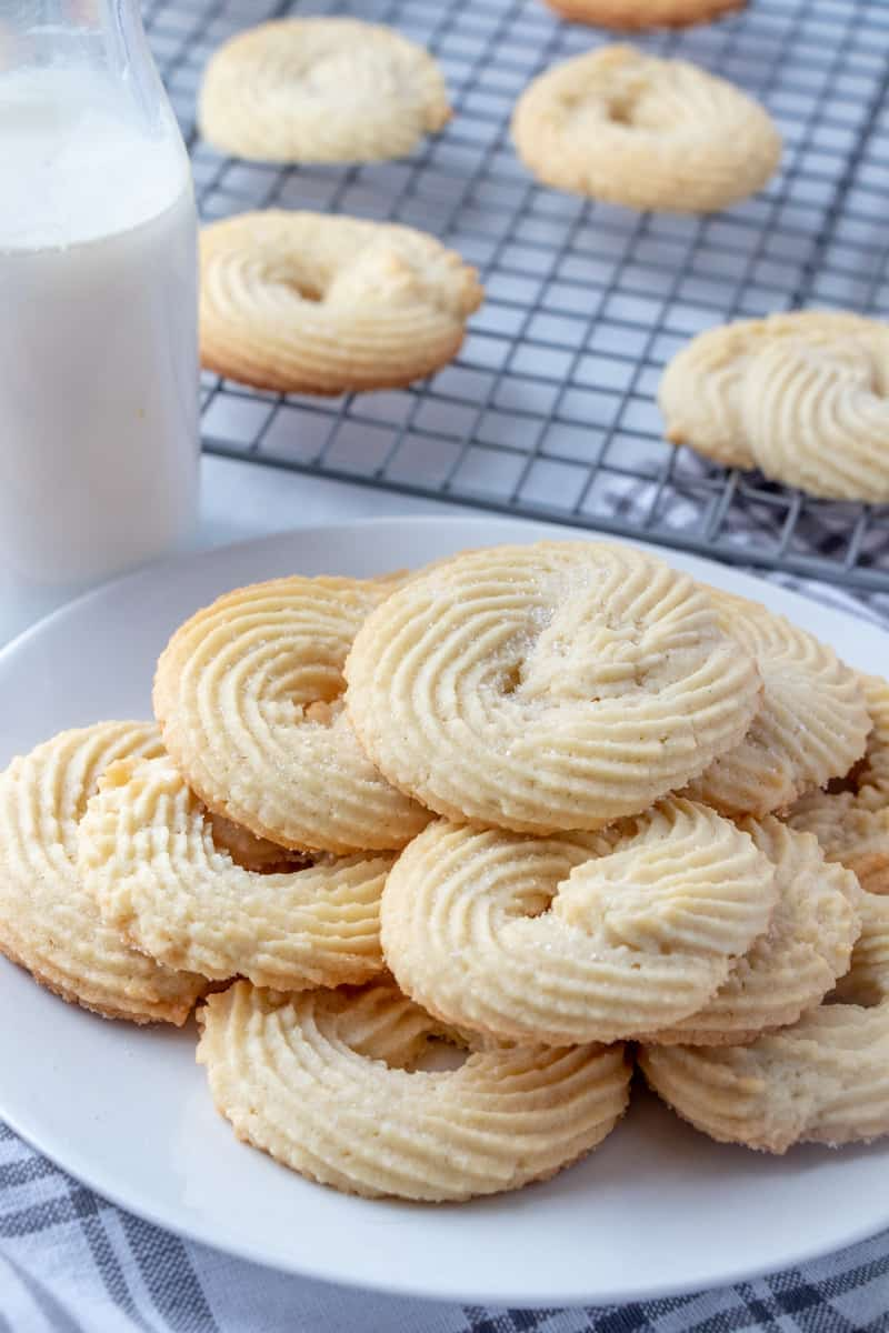 Plateful of cookies with cooling rack in background with cookies on it