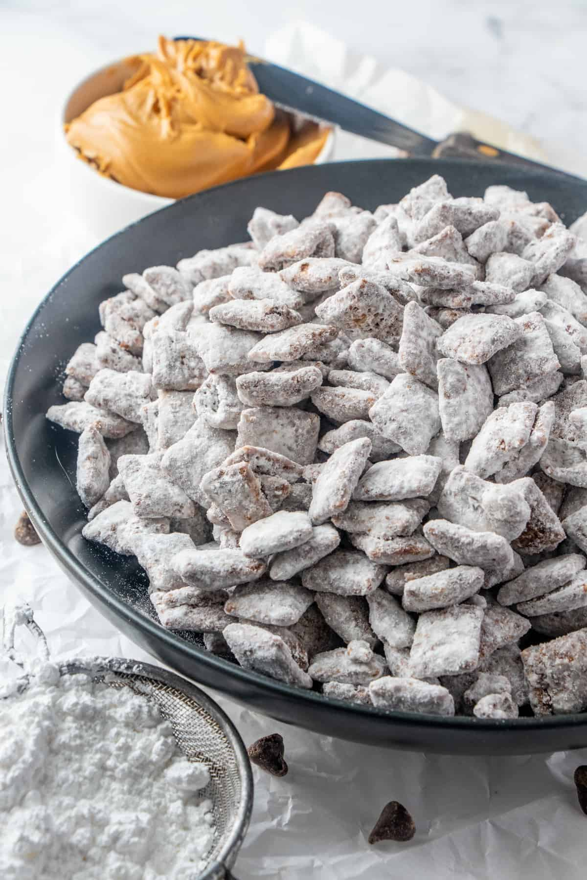 Puppy Chow in black bowl with bowl of peanut butter and sifter of powdered sugar