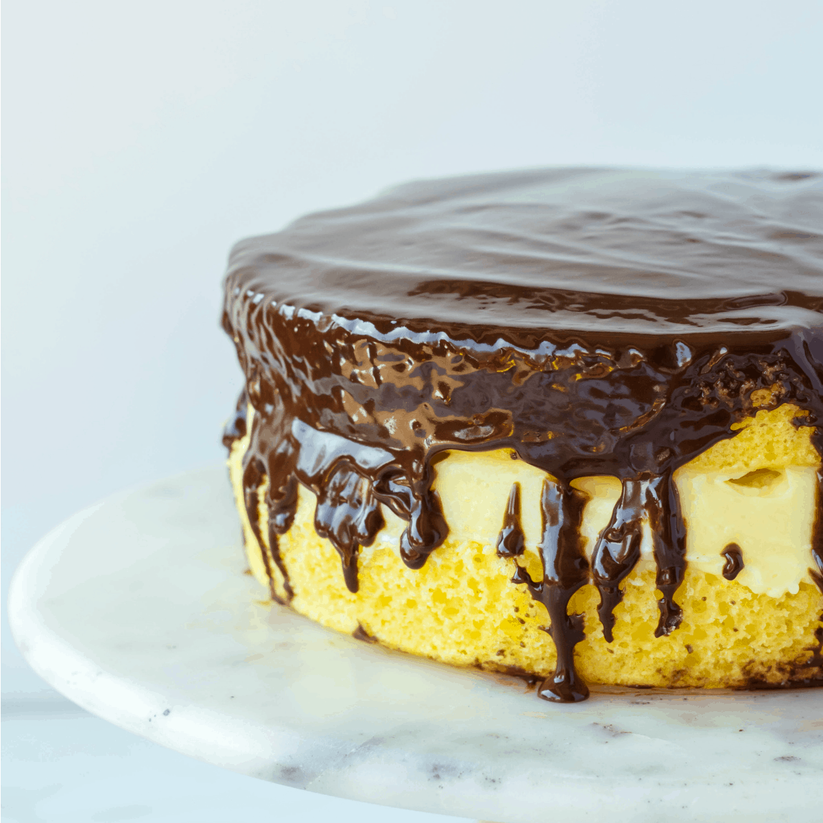Boston Cream Pie on cake stand drizzled with ganache