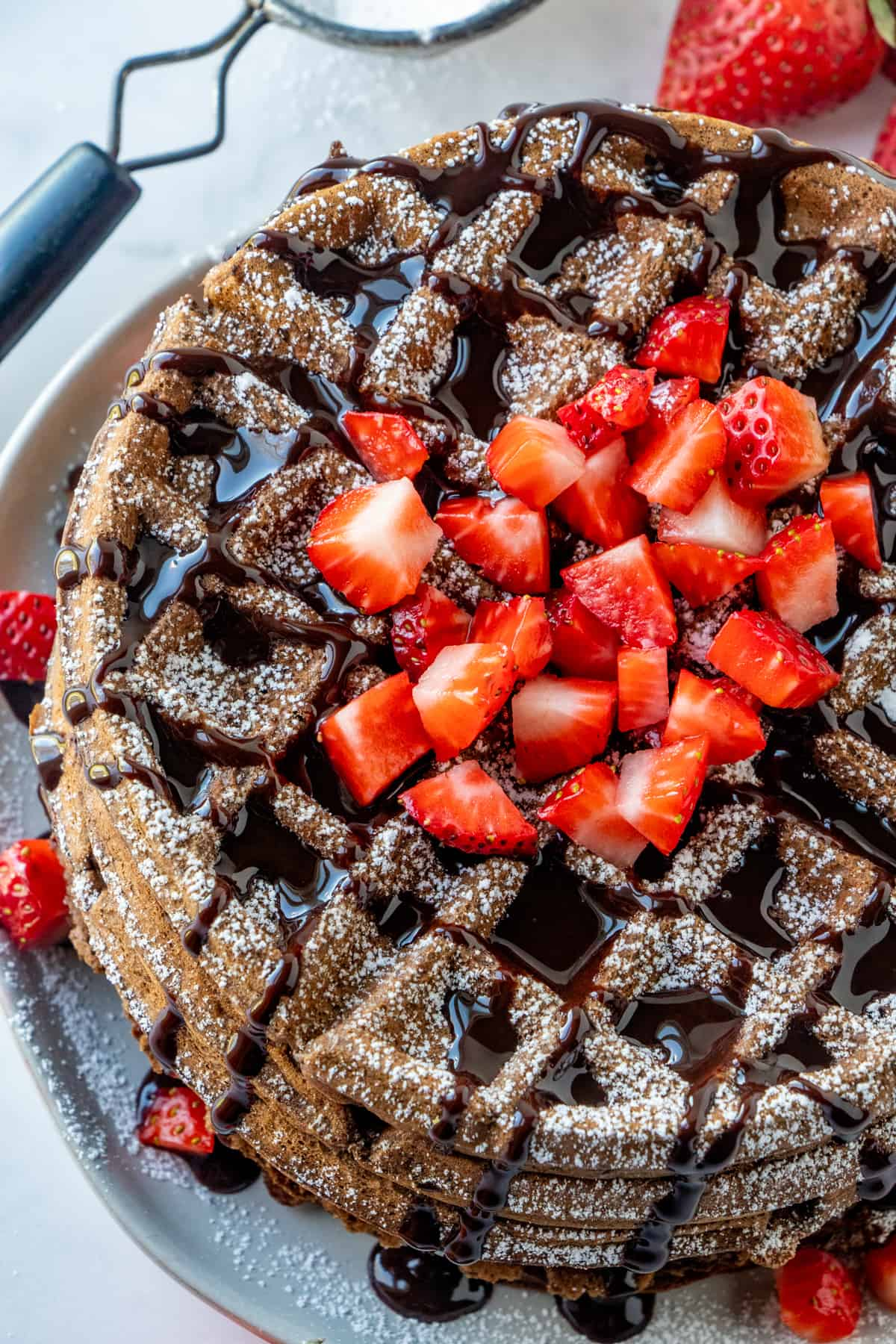 Overhead photo of chocolate waffles toped with powdered sugar, chocolate syrup and strawberries