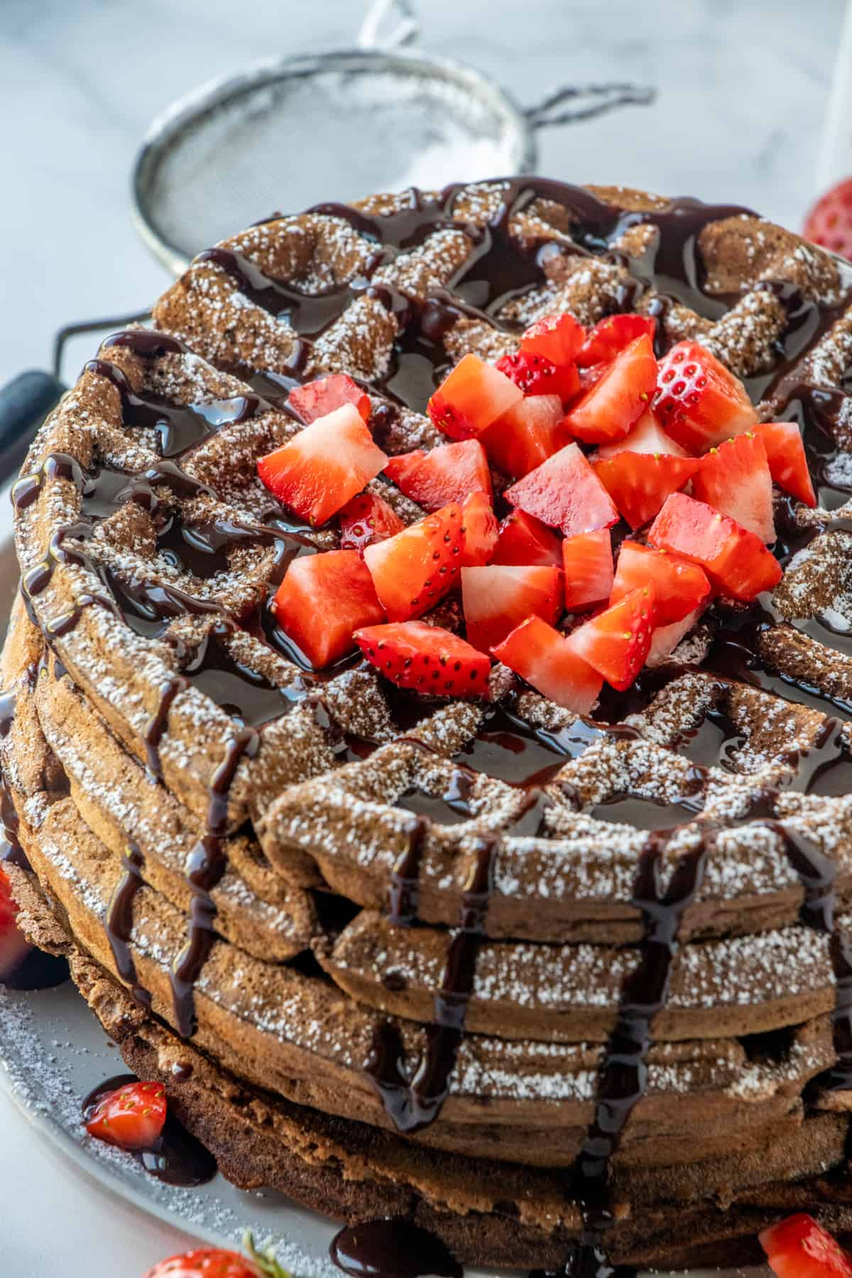 Close up photos of chocolate waffles showing chocolate syrup dripping down the side