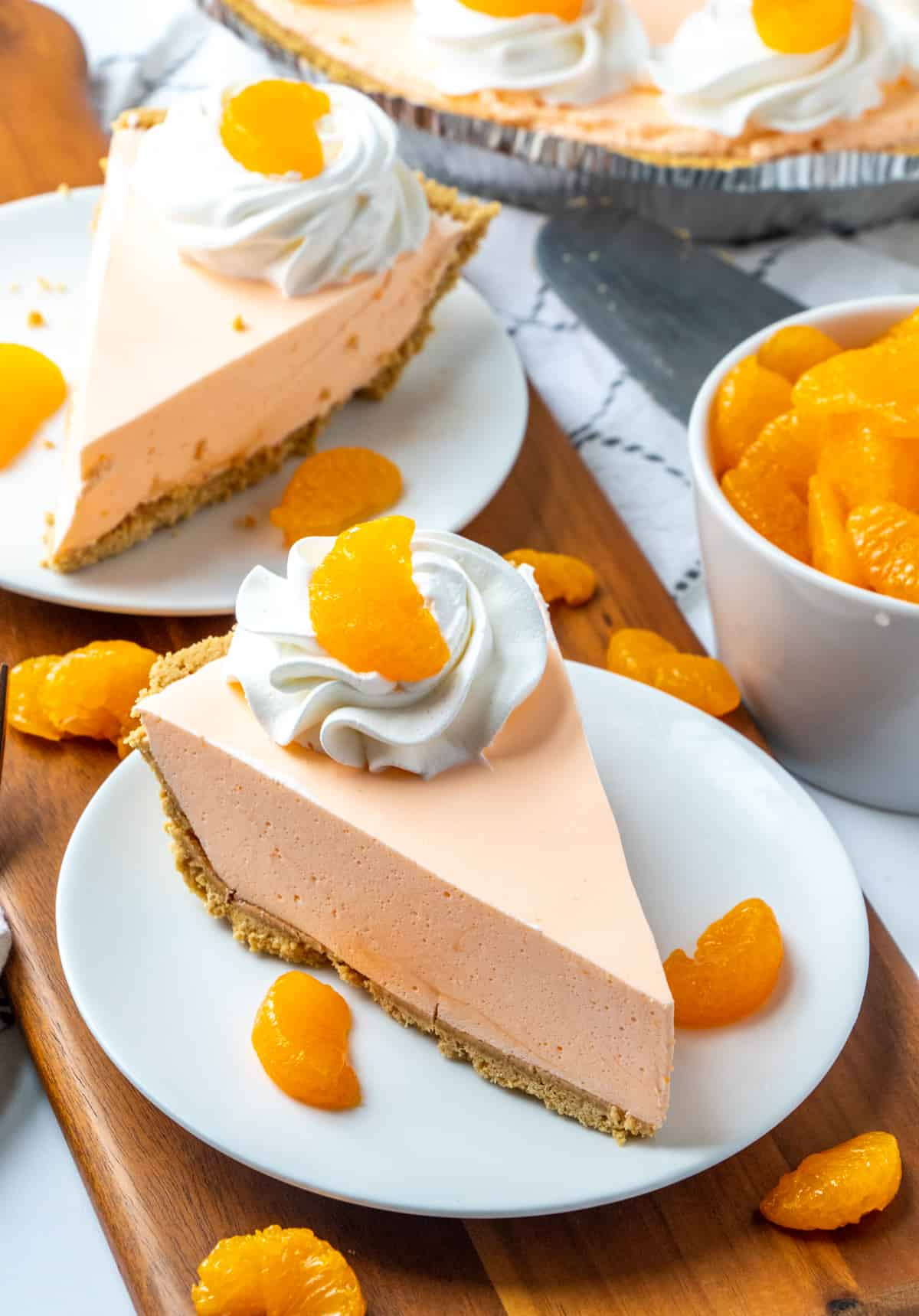 Two slices of pie on white plates topped with whipped cream and mandarin orange