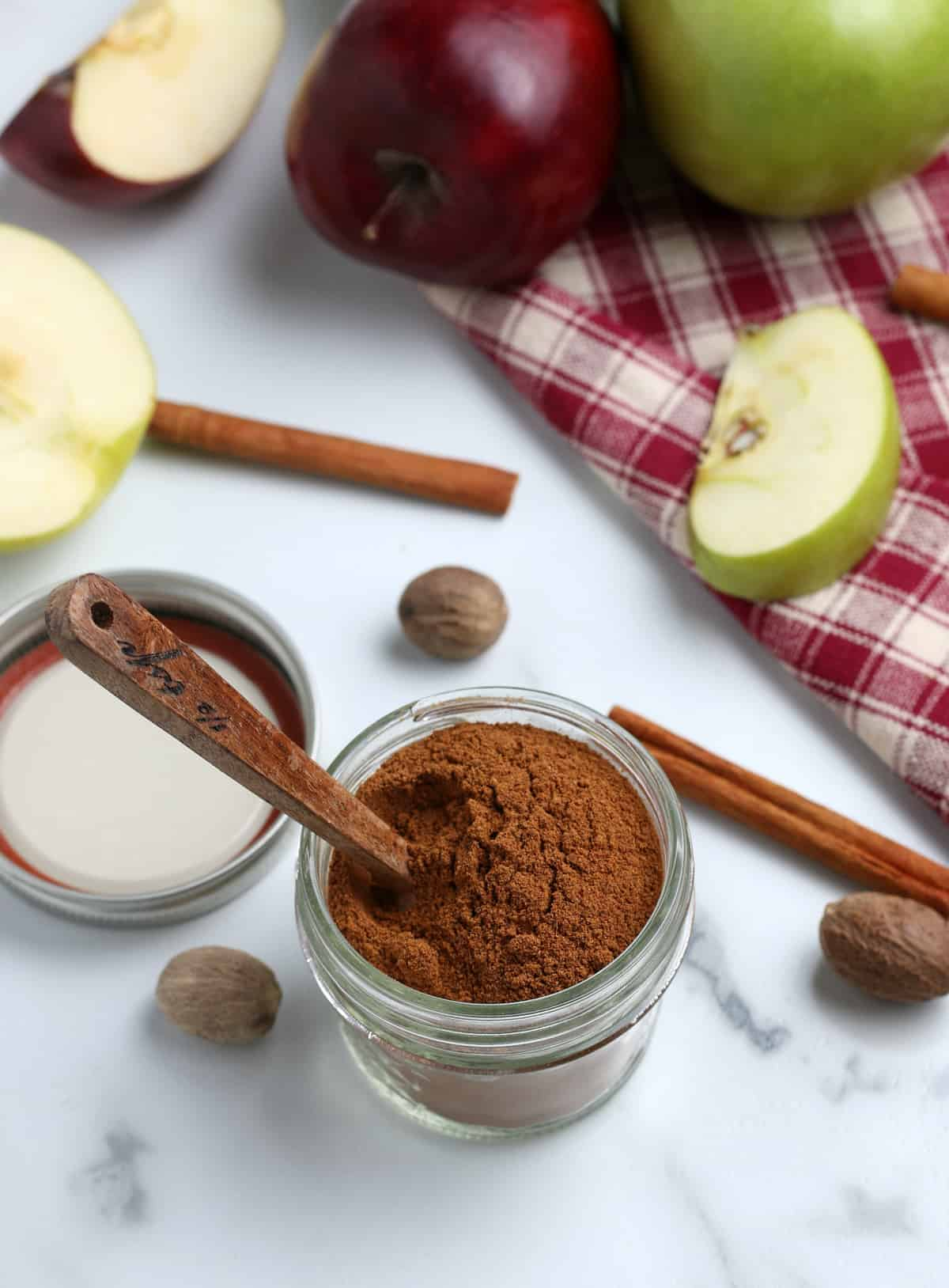 Apple Pie Spice in jar with spoon surrounded by apples and cinnamon