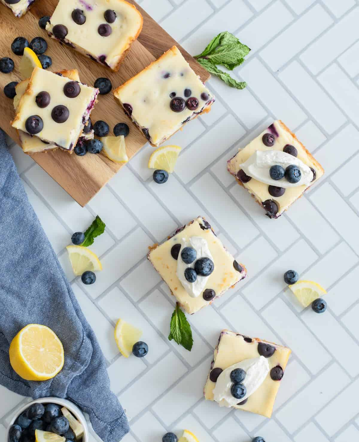 Overhead of cut cheesecake bars garnished with blueberries and lemons