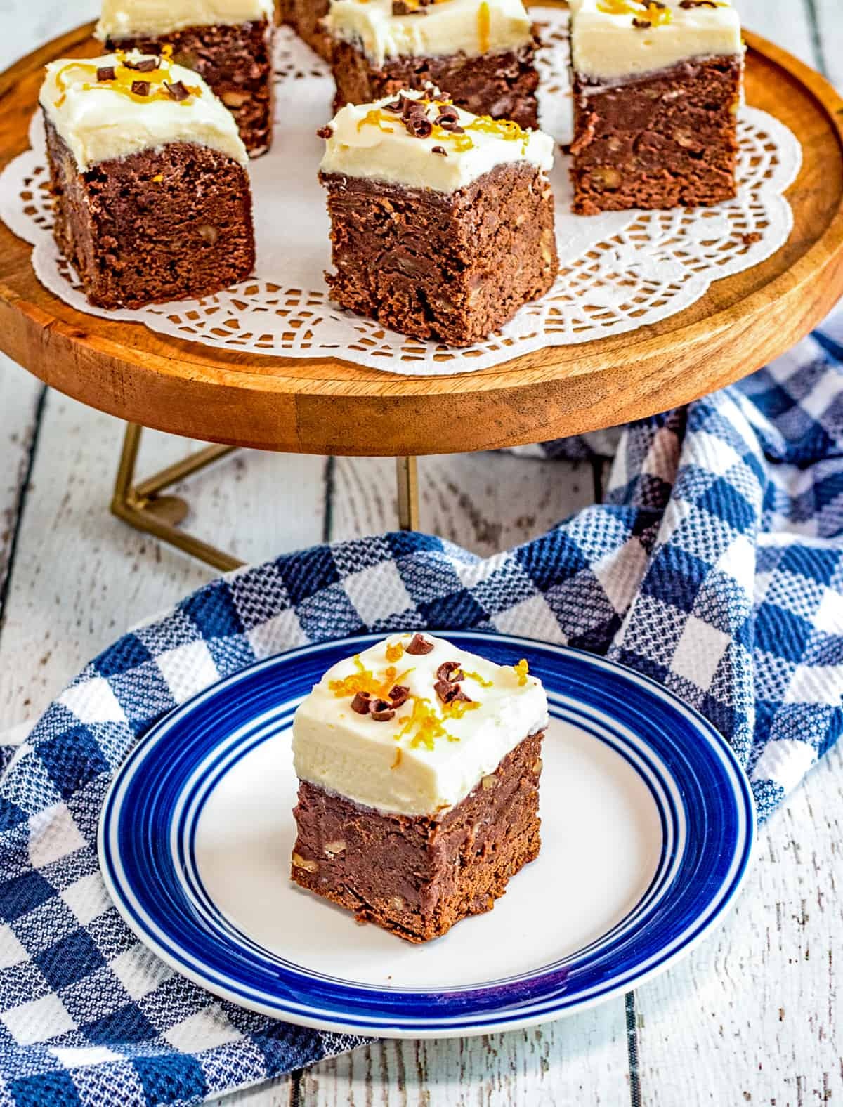 Chocolate Orange Brownie on white and blue plate with cut brownies on cake stand
