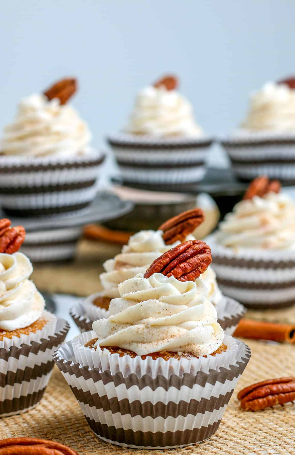 Close up of one frosted pumpkin cupcake topped with pecan