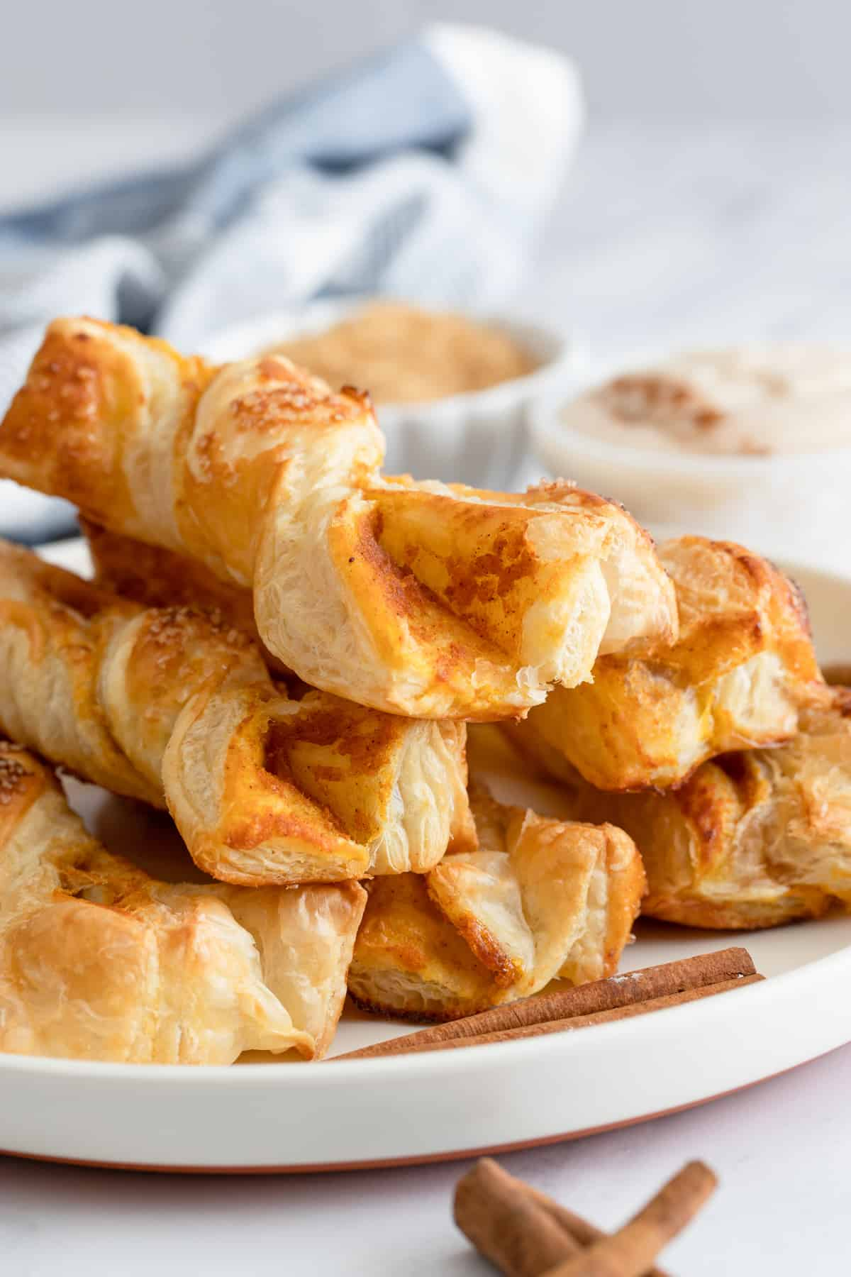 Close up of Pumpkin Puff Pastry Twists stacked on white plate