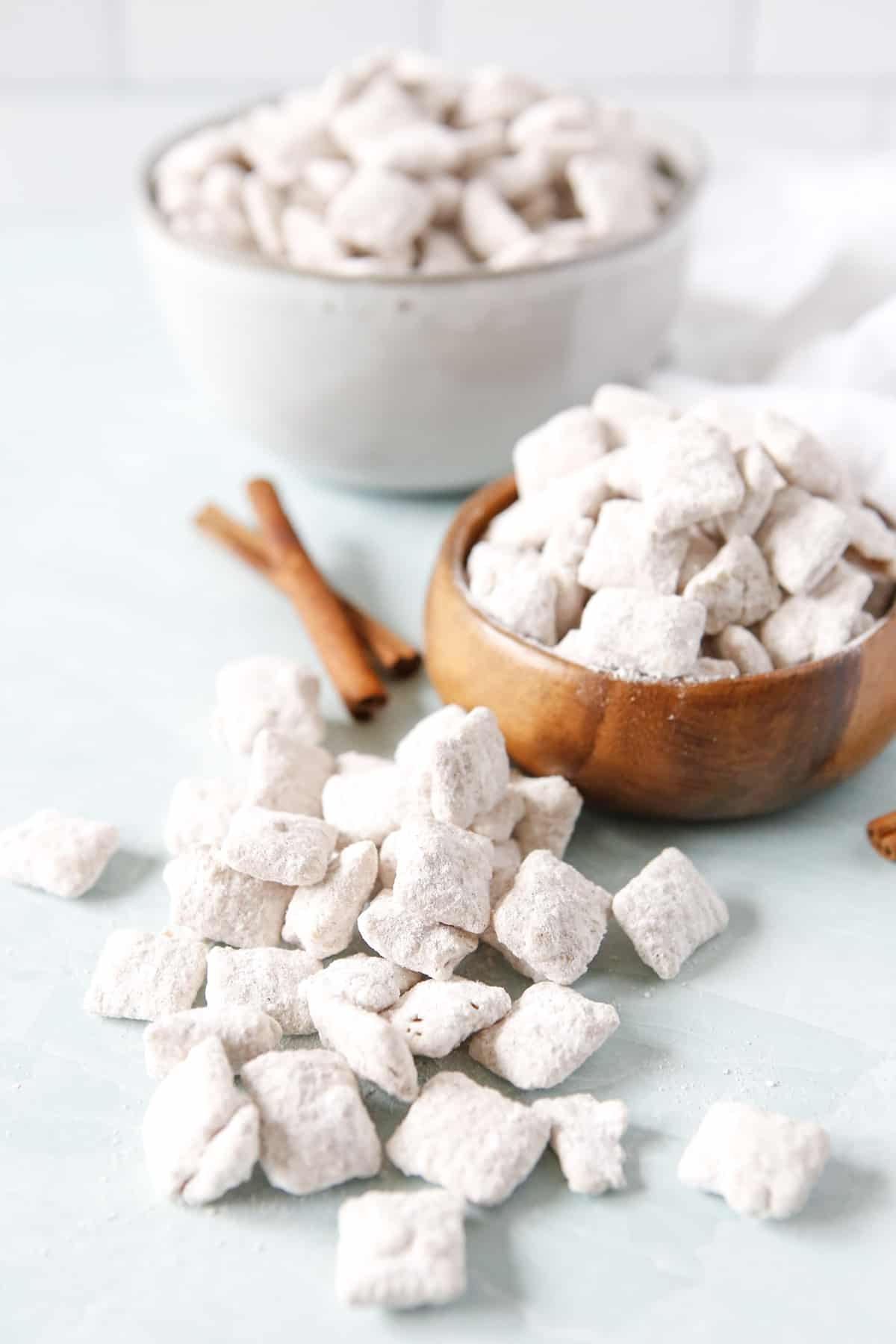 Small wooden bowl of Snickerdoodle Puppy chow with some laying in front of it