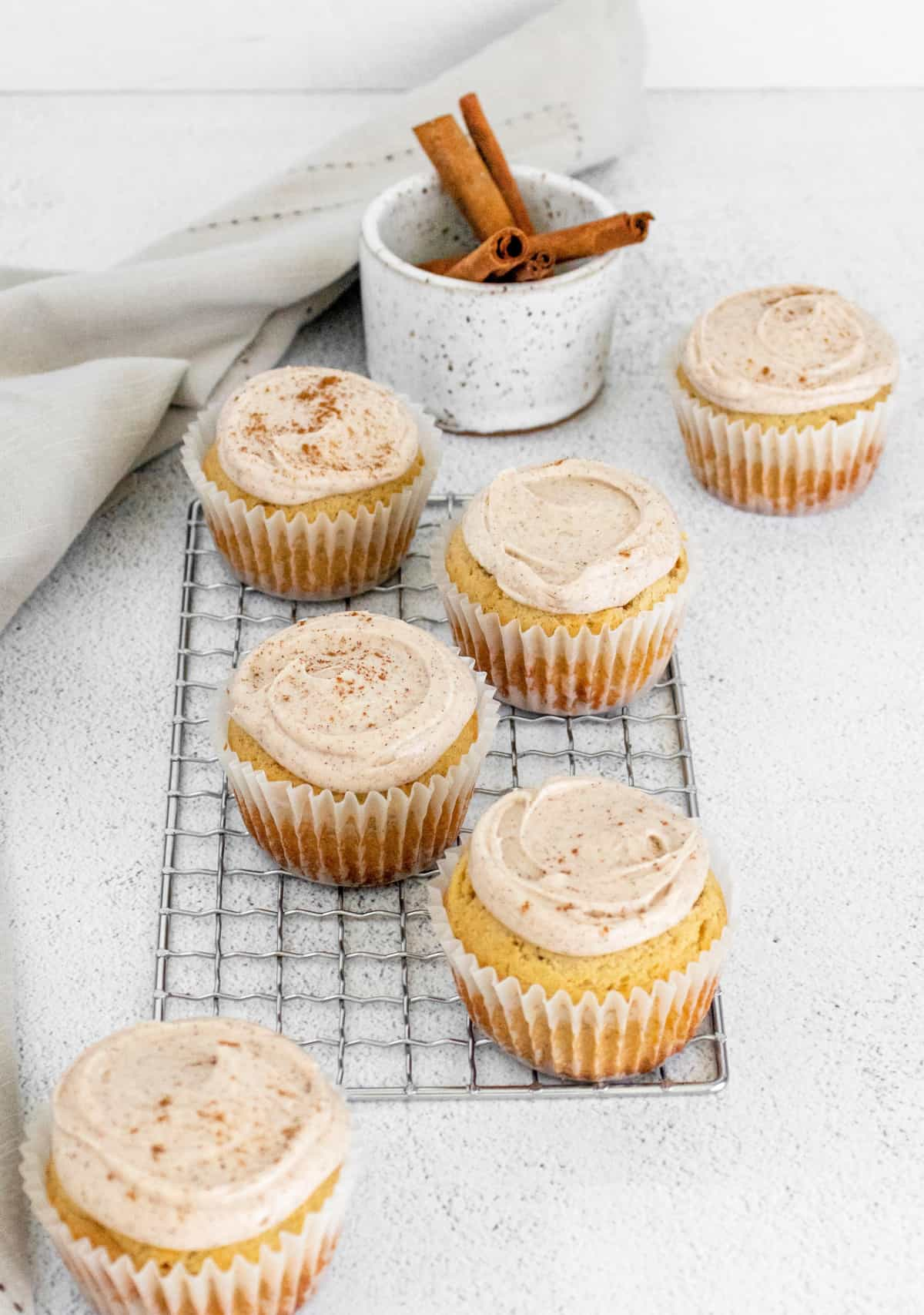 Frosted Cinnamon Cupcakes on wire rack with cinnamon sticks in background