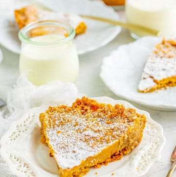 Slices of Crack Pie on white plates with glass of milk