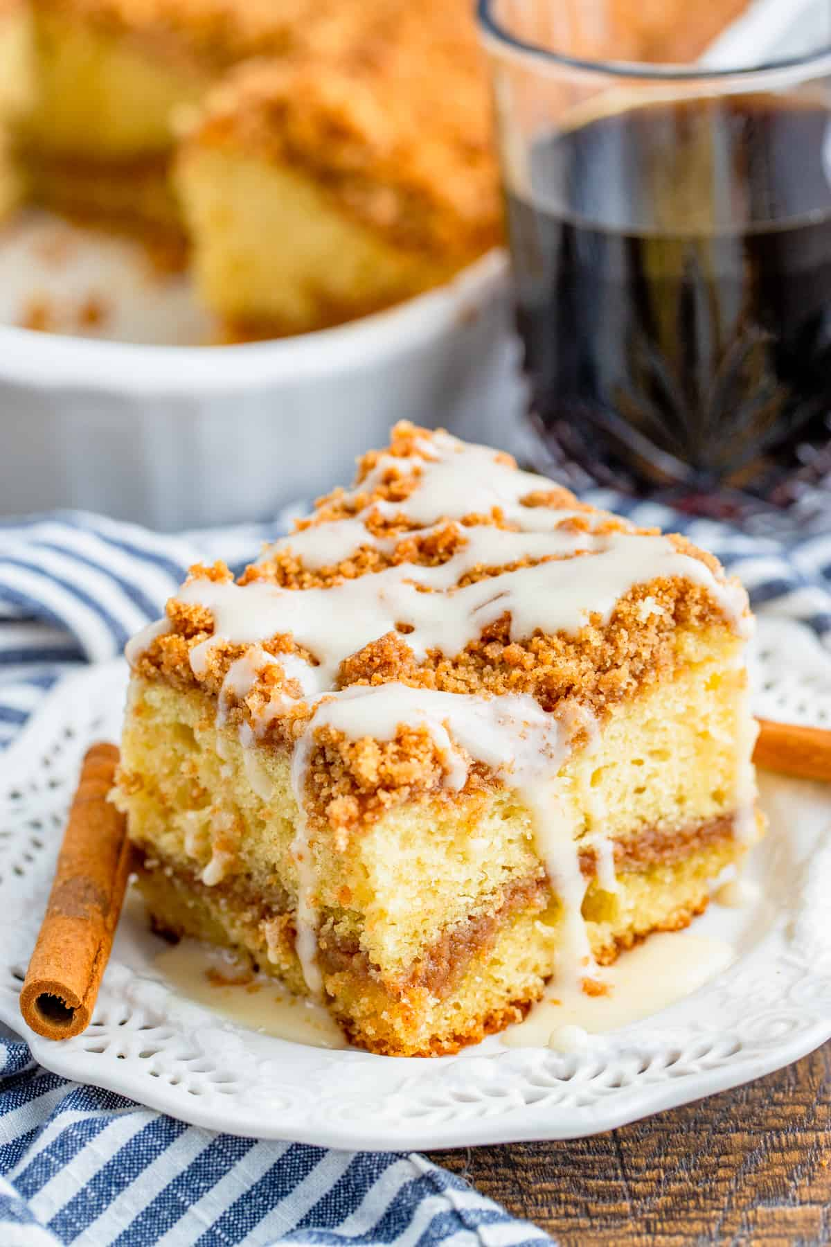 Slice of Sour Cream Coffee Cake on white plate with cinnamon