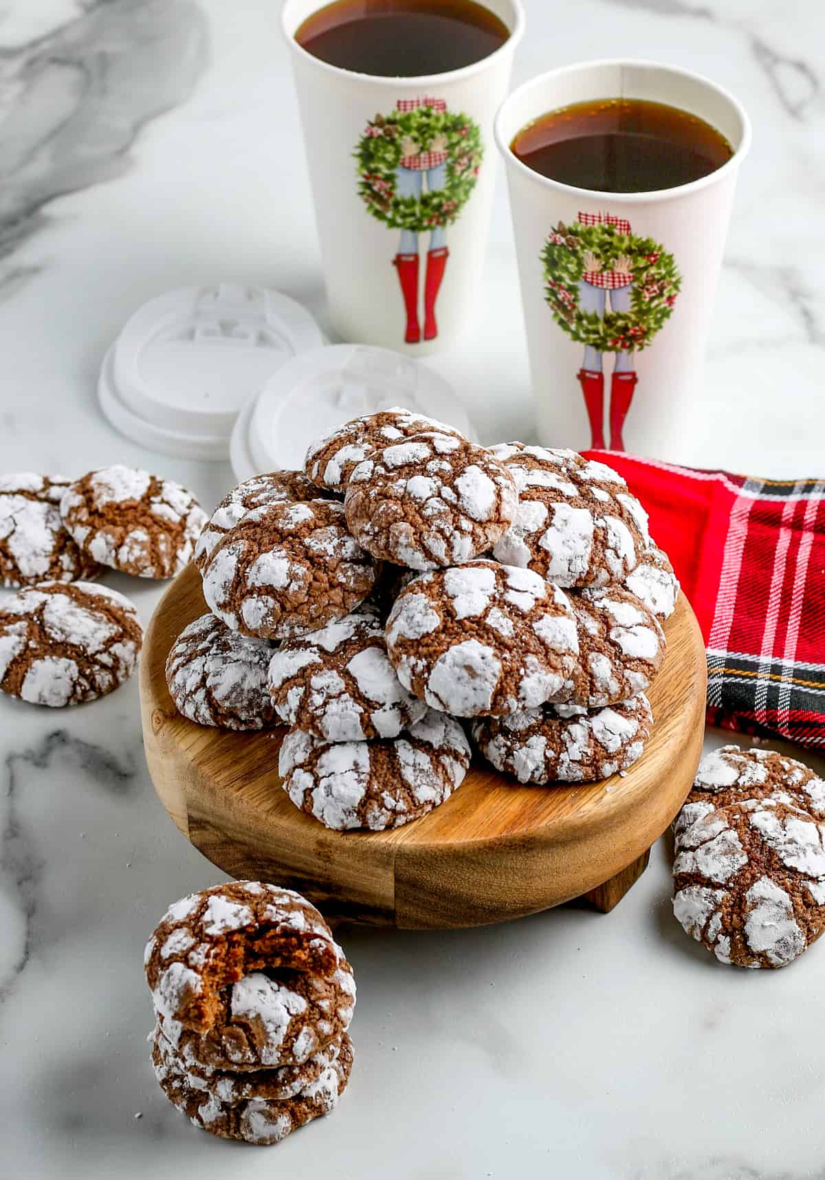 Chocolate Crinkles on wooden stand stacked with coffee in background