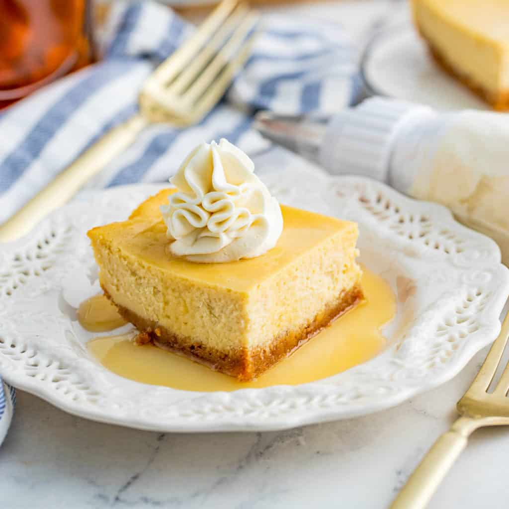 Cheesecake Bar on white plate with gold forks square image