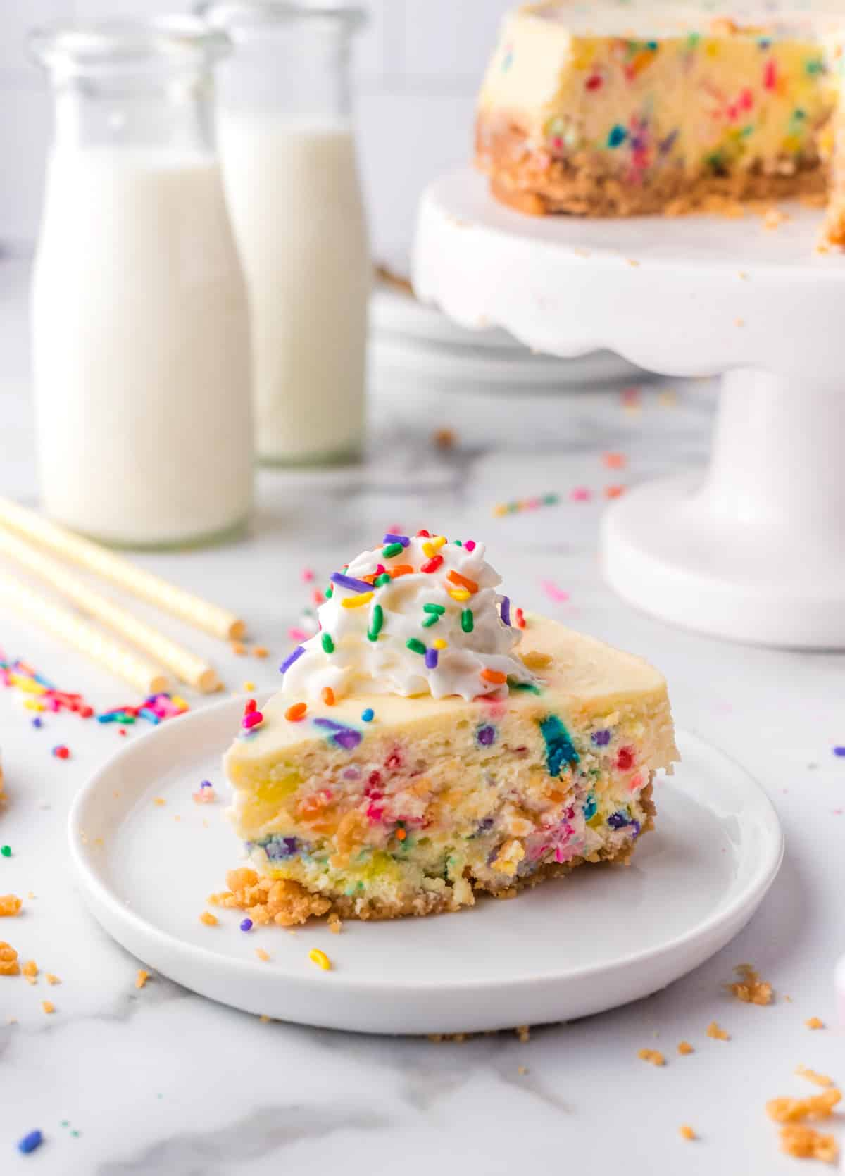 Slice of cut Funfetti Instant Pot Cheesecake on white plate