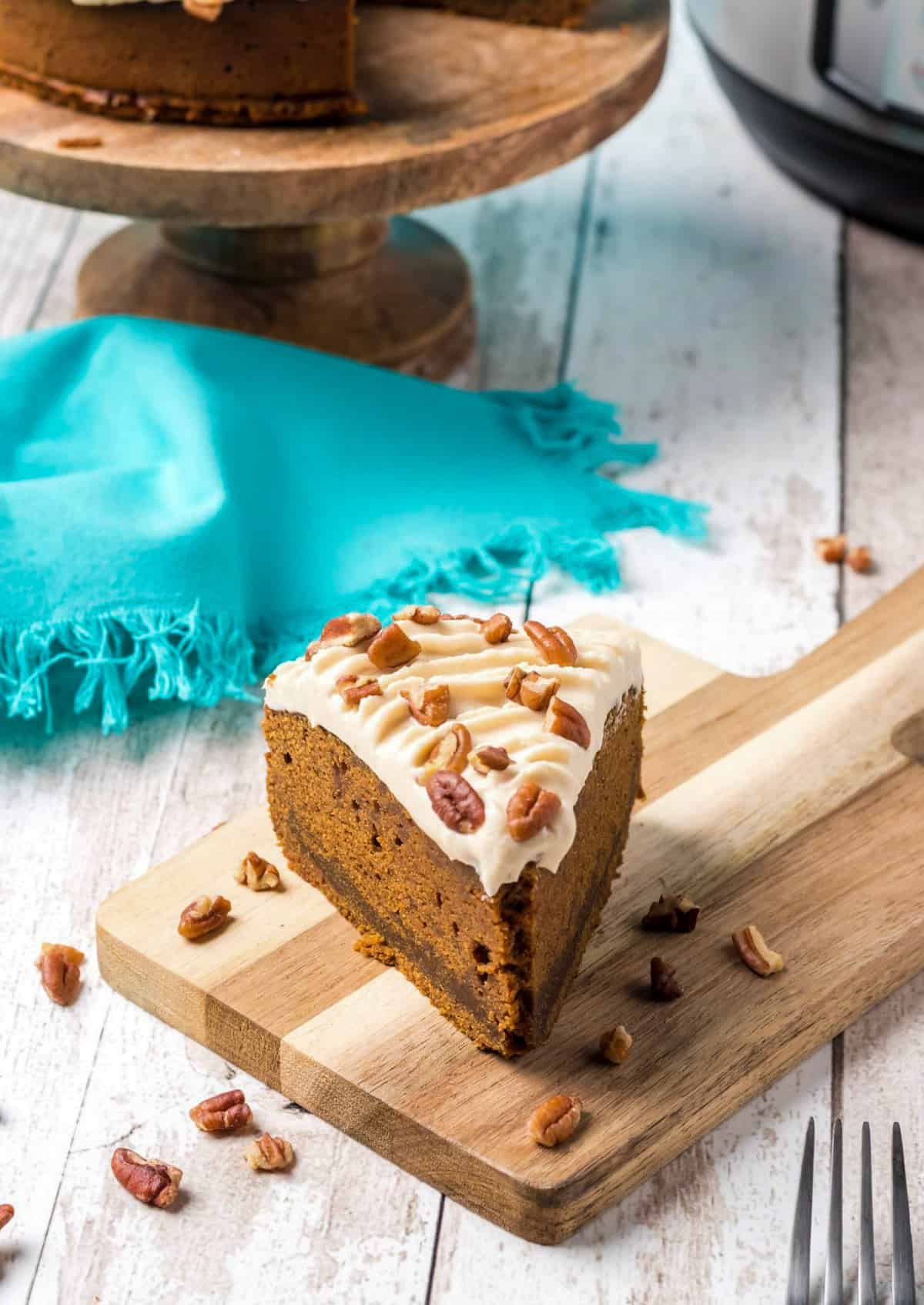 Slice of Gingerbread Cake on cutting board surrounded by nuts