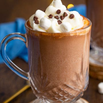 Clear mug of Spiked Hot with whipped cream, marshmallows and chocolate chips
