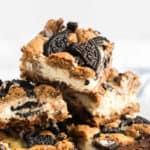 Close up of stacked Chocolate Chip Oreo Cheesecake Bars square image