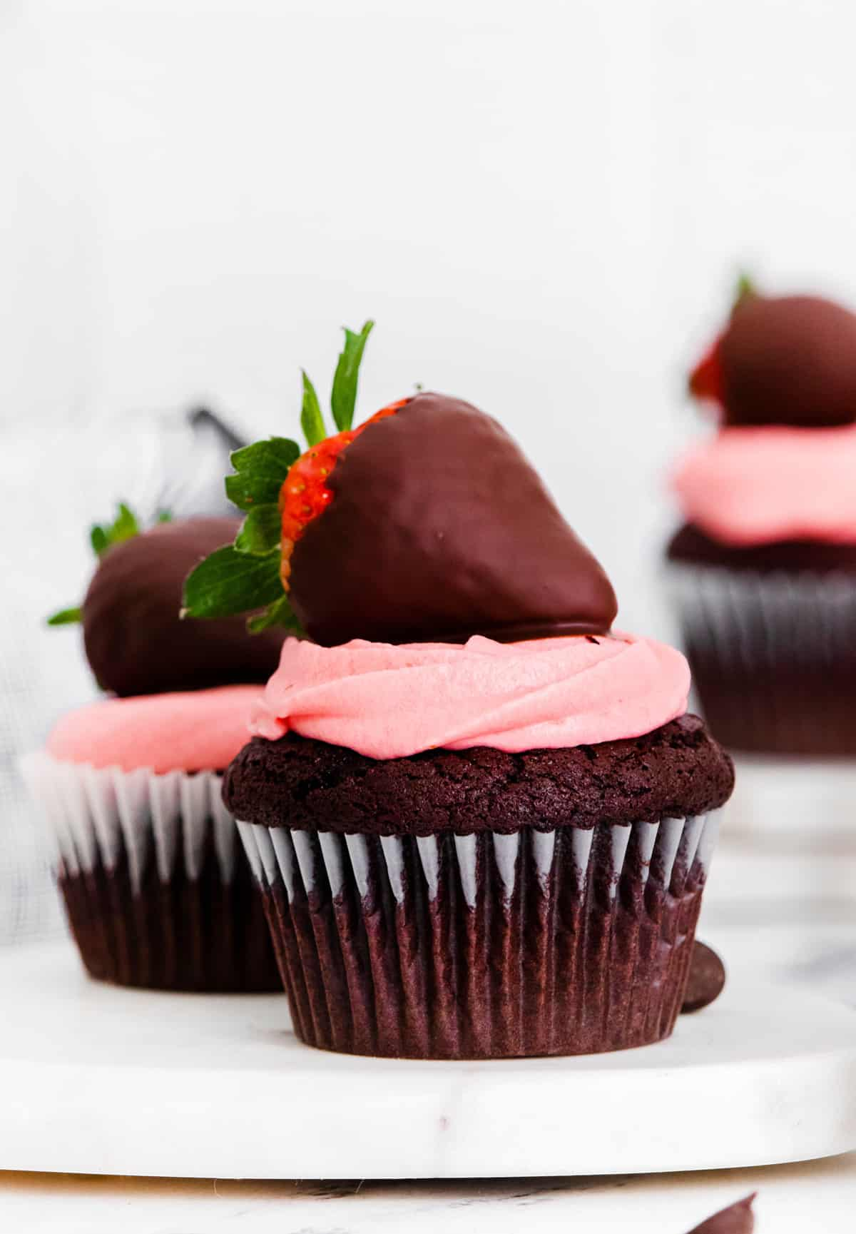 Close up of one Chocolate Covered Strawberry Cupcake on white platter