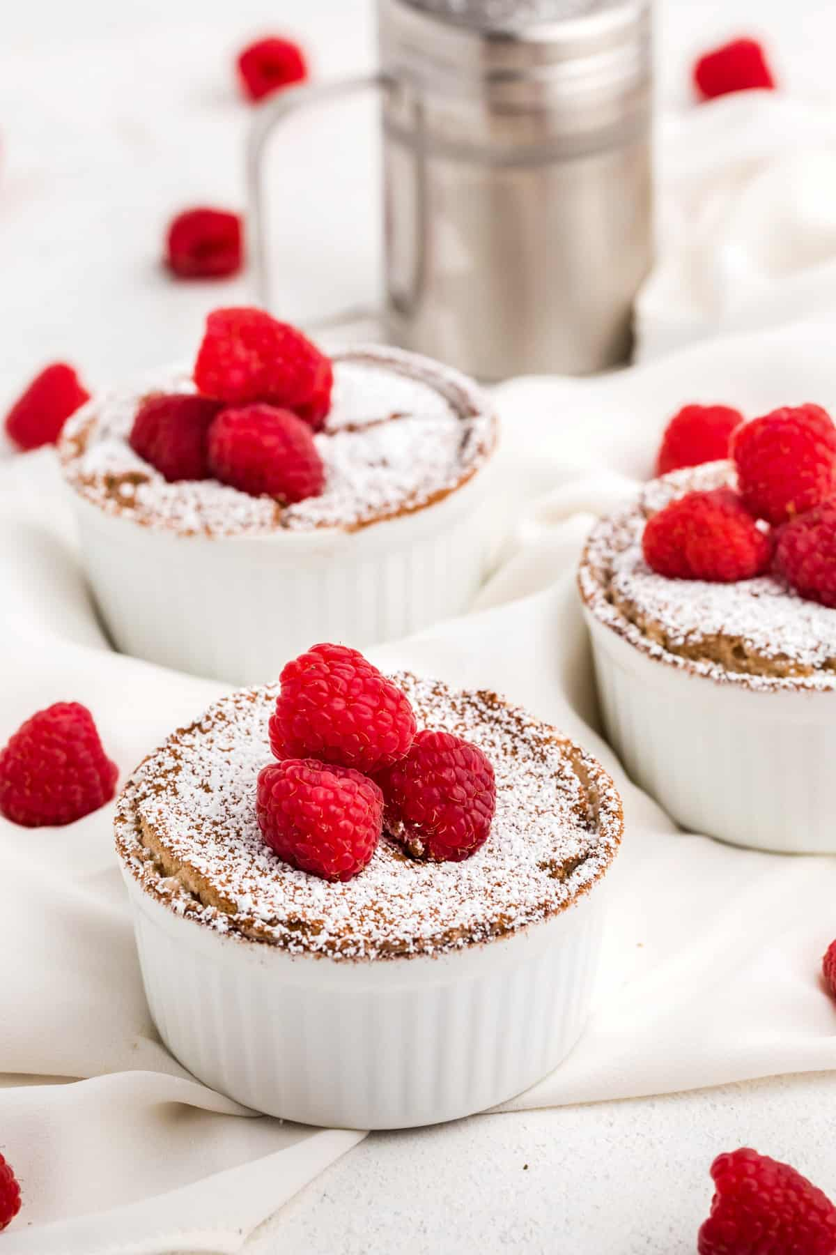 Chocolate Soufflés topped with powdered sugar and raspberries