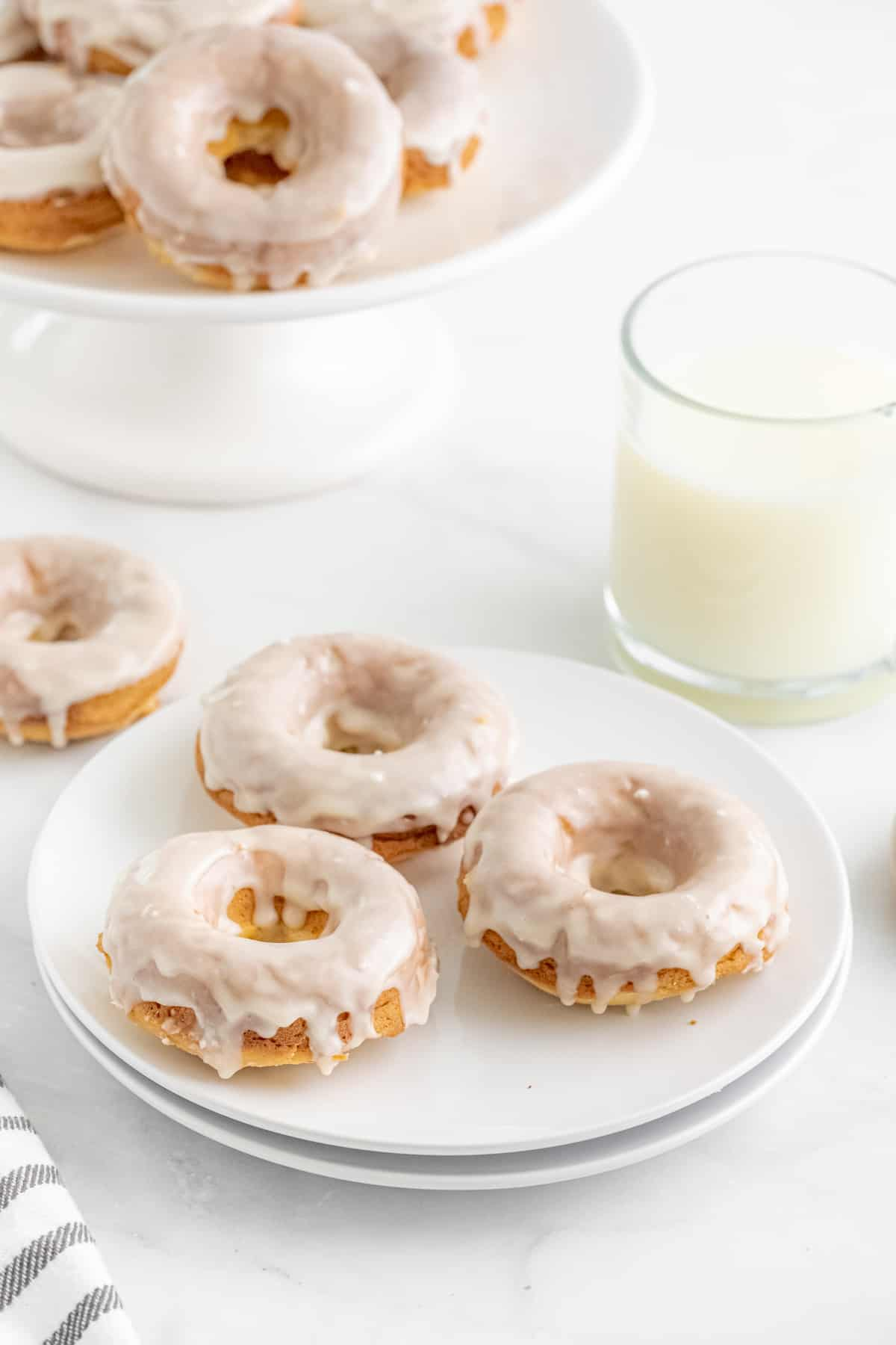 Three Baked Donuts on white plate with more on cake stand in background