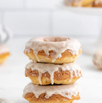 Three stacked Vanilla Glazed Baked Donuts with glaze dripping down sides