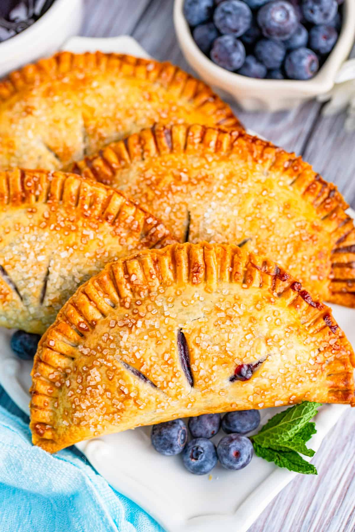 Overhead of stacked Air Fryer Blueberry Hand Pies on white platter