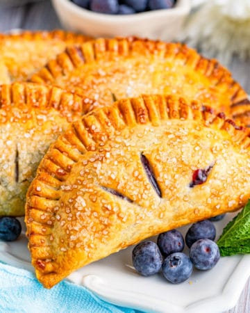Close up of one Hand Pie on platter with berries square image