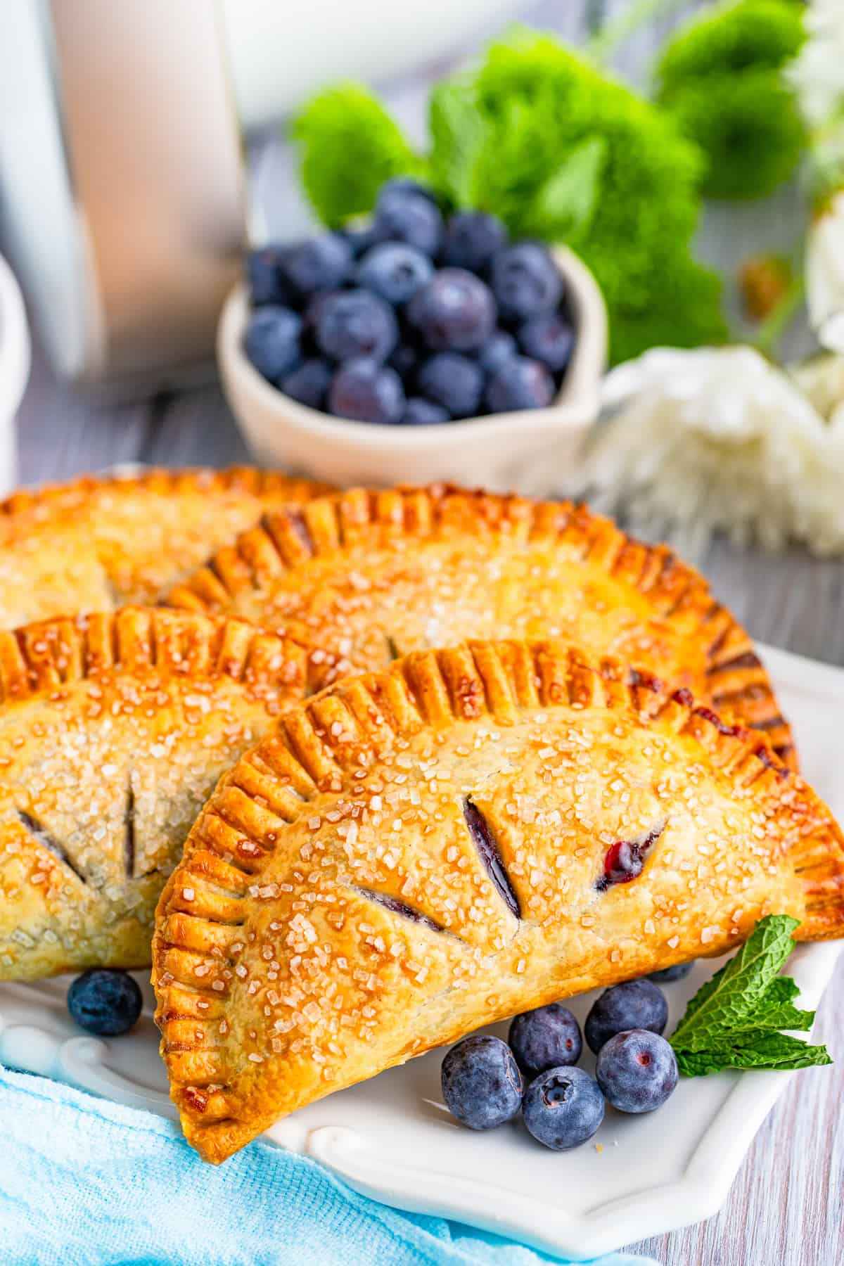 Side view of layered Hand Pies on platter with blueberries and mint