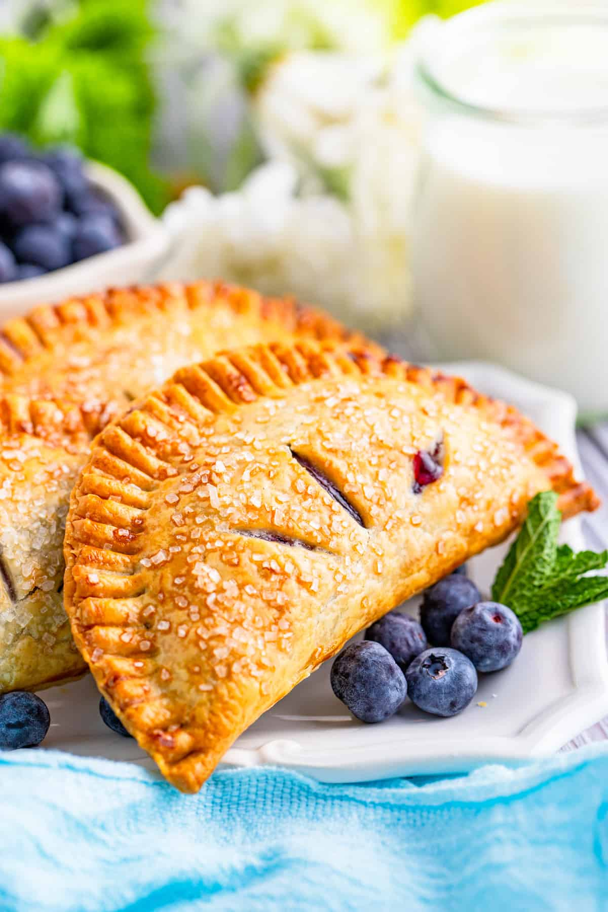Close up side view of one Blueberry Hand Pie on white platter with blueberries