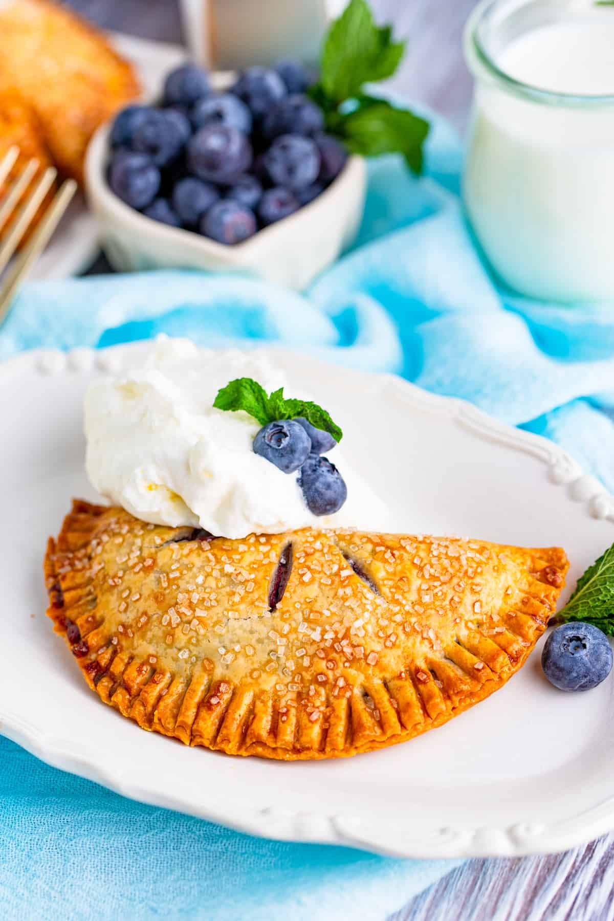 One Air Fryer Blueberry Hand Pie on plate with whipped topping and blueberries