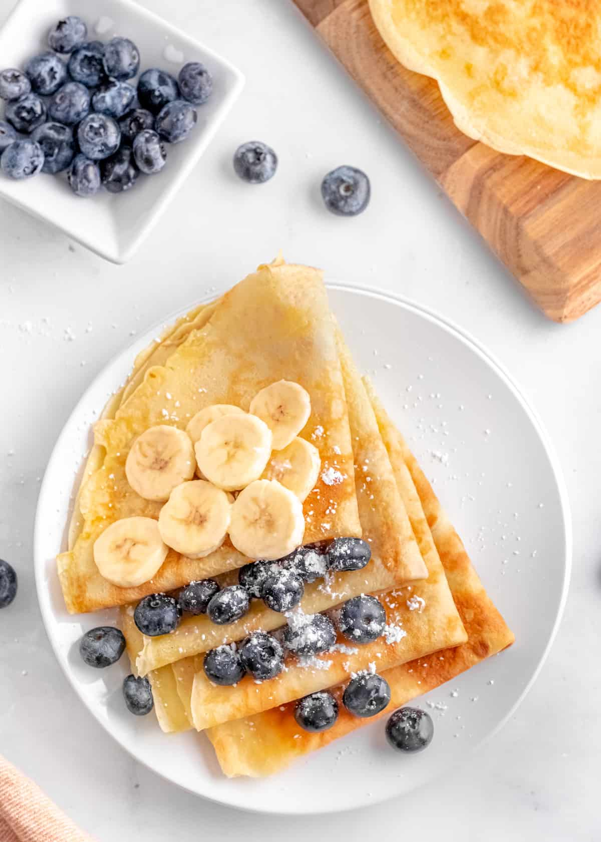 Overhead photo of Easy Crepes on plate topped with fruit and powdered sugar