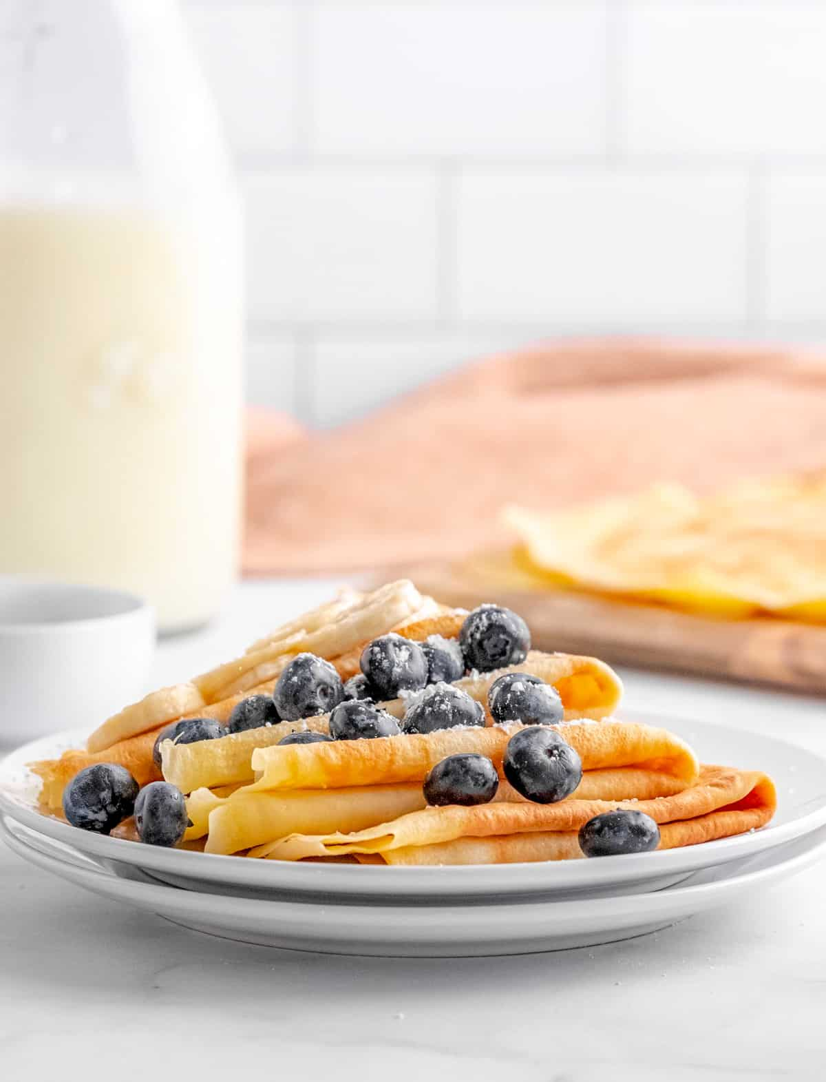 Side view of Easy Crepes on white plate topped with fruit