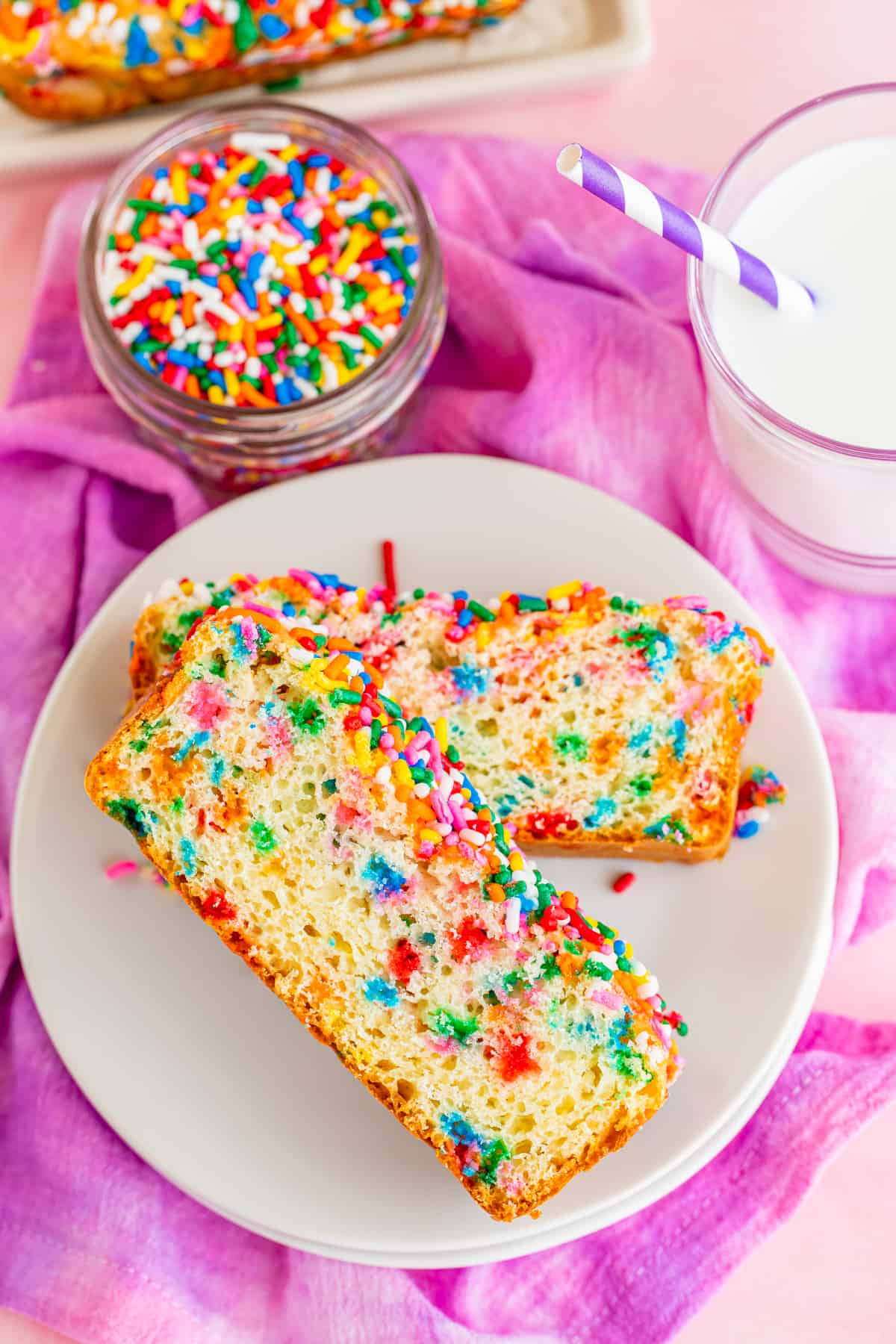 Two slices of bread on white plate with sprinkles and milk by plate