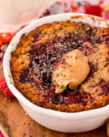 Square photo of finished Peanut Butter & Jelly Baked Oats in dish garnished