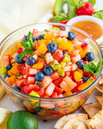 Salsa in bowl surrounded by cinnamon chips and fruit