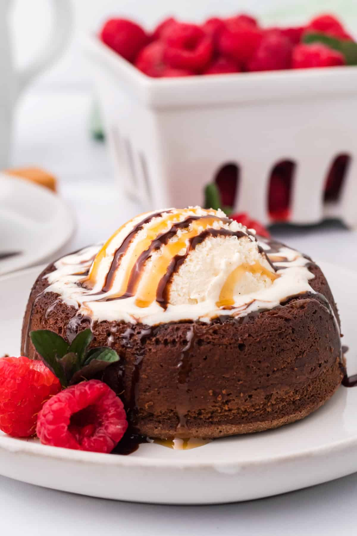 Side view of Lava Cake on white plate with raspberries