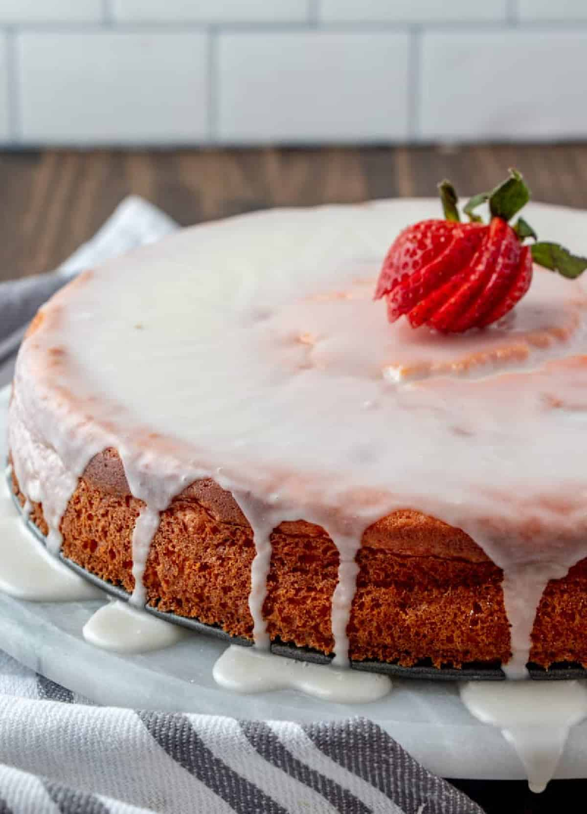 Whole cake on turntable glazed and topped with a strawberry