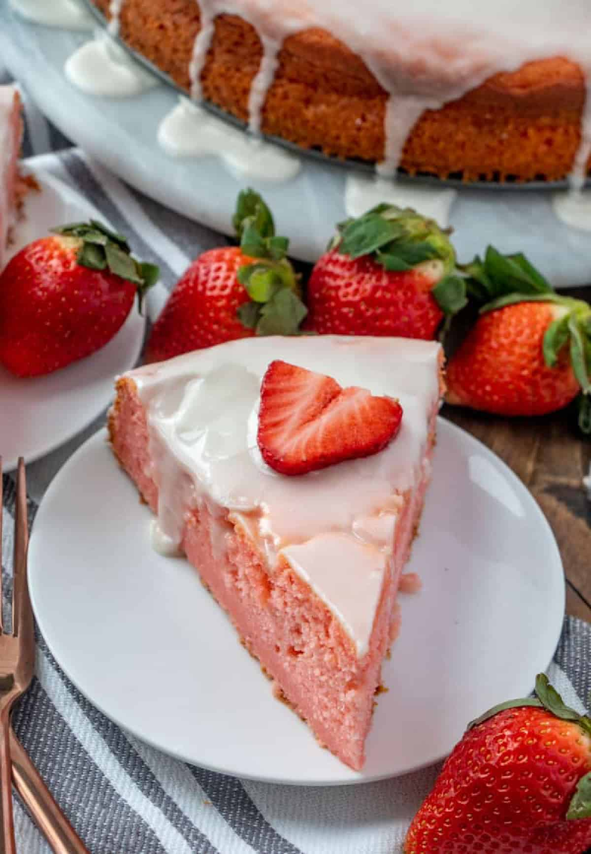 Overhead of slice of Ricotta Cake on white plate topped with strawberry