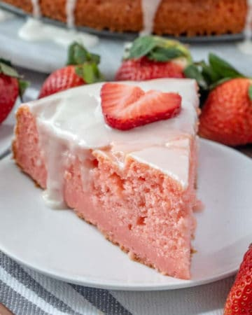 Square photo of cake on white plate topped with icing and strawberry