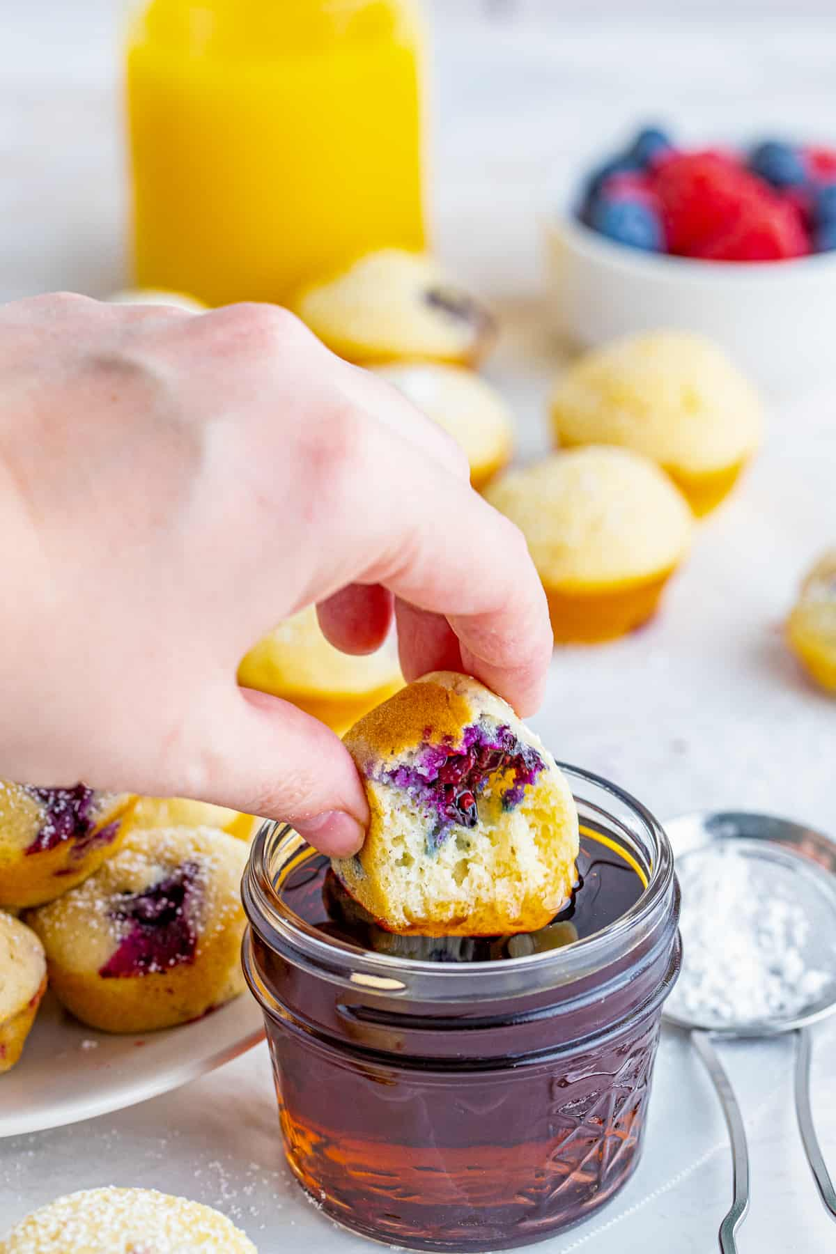 Hand dipping one Berry Pancake Bites in syrup