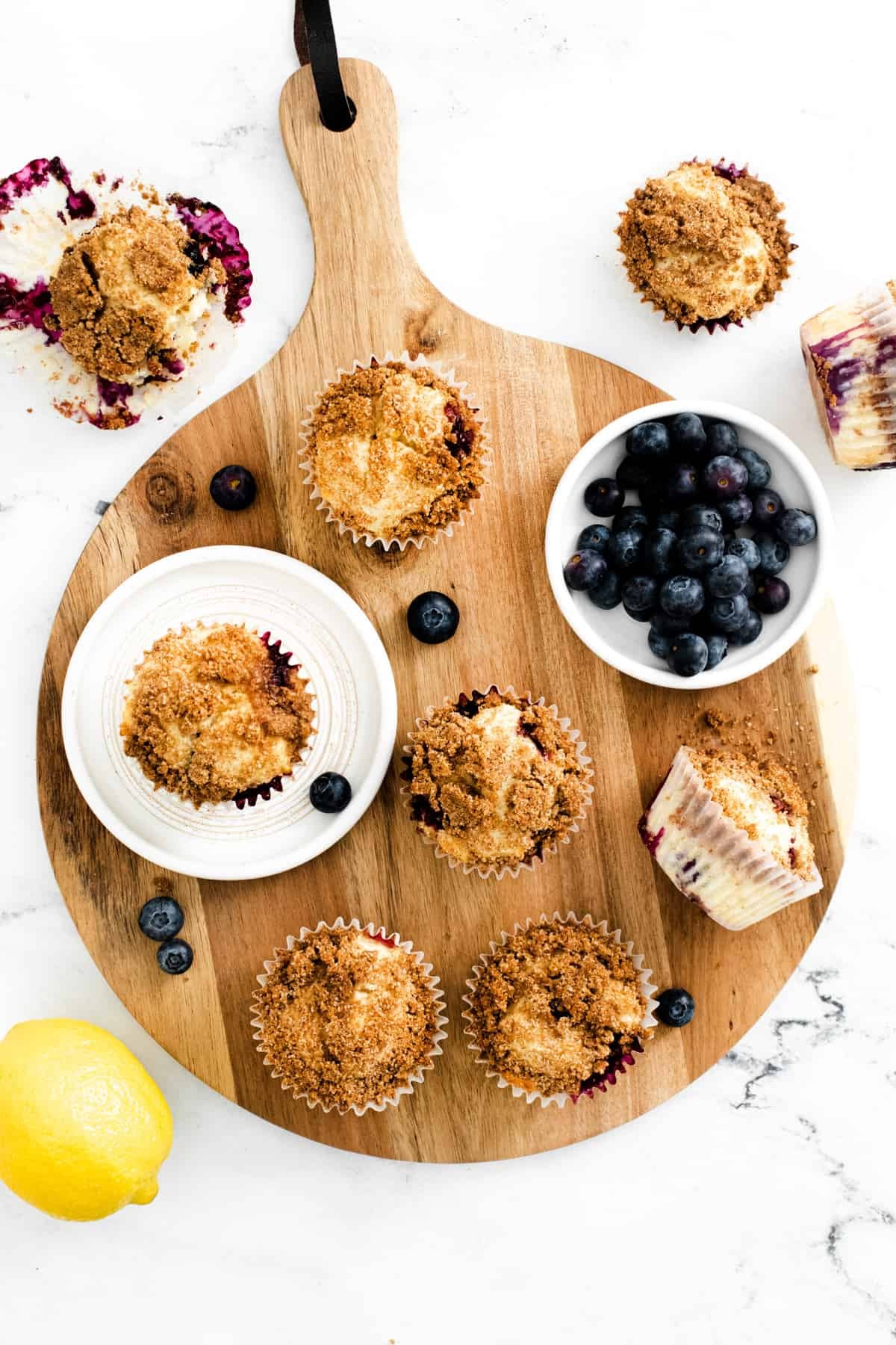 Overhead photo of muffins on wooden board with blueberries