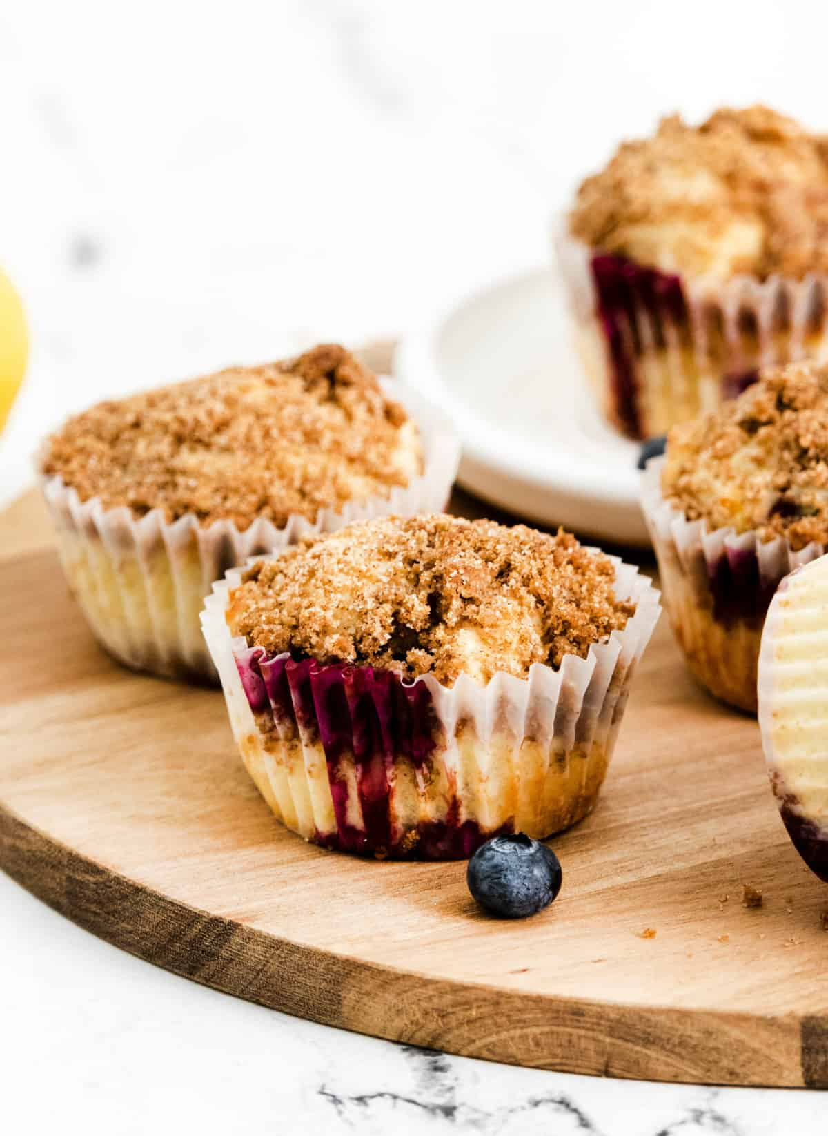 Lemon Blueberry Muffins on wooden platter showing side of muffins