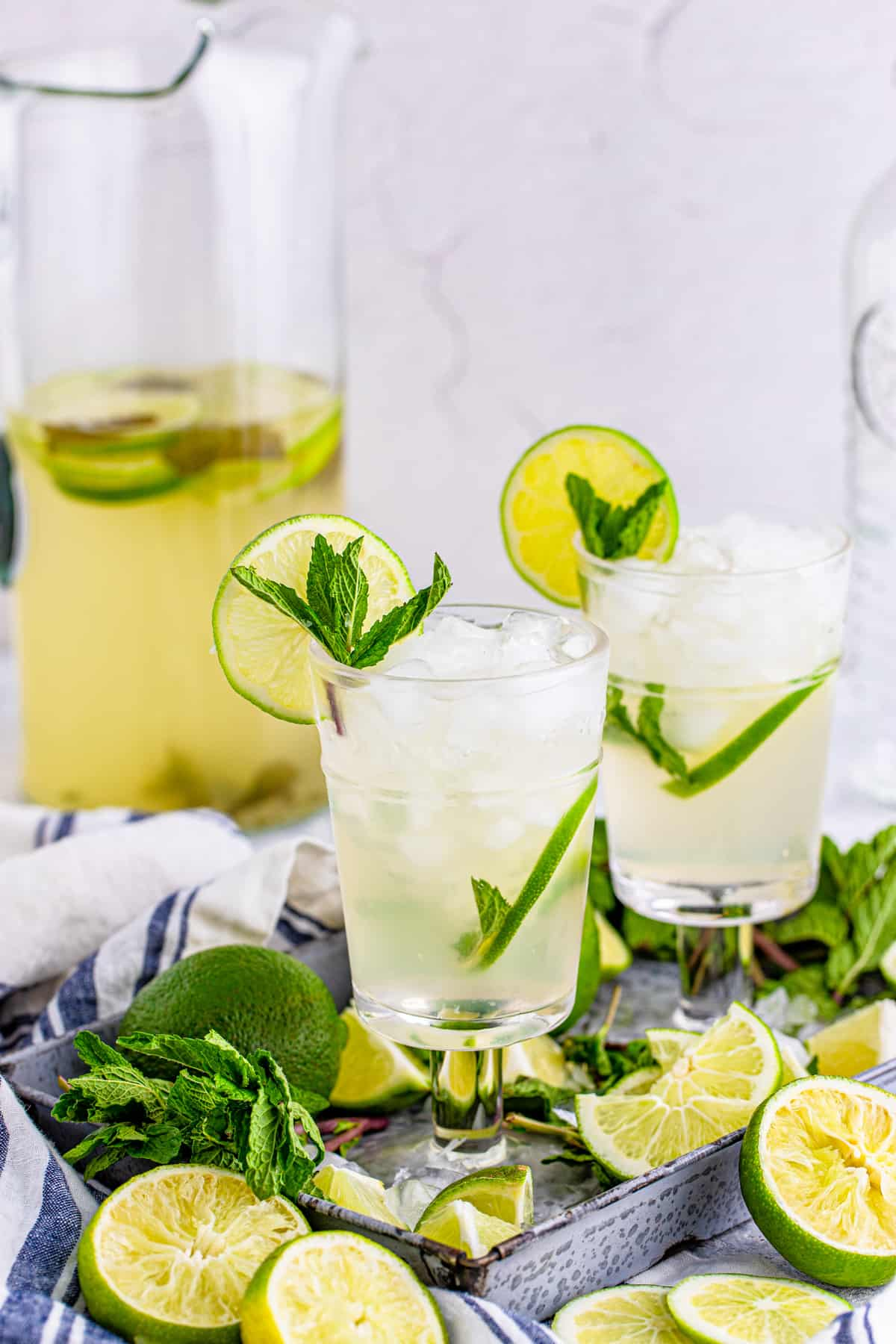 Two glasses of Pitcher Mojitos on tray with limes and mint