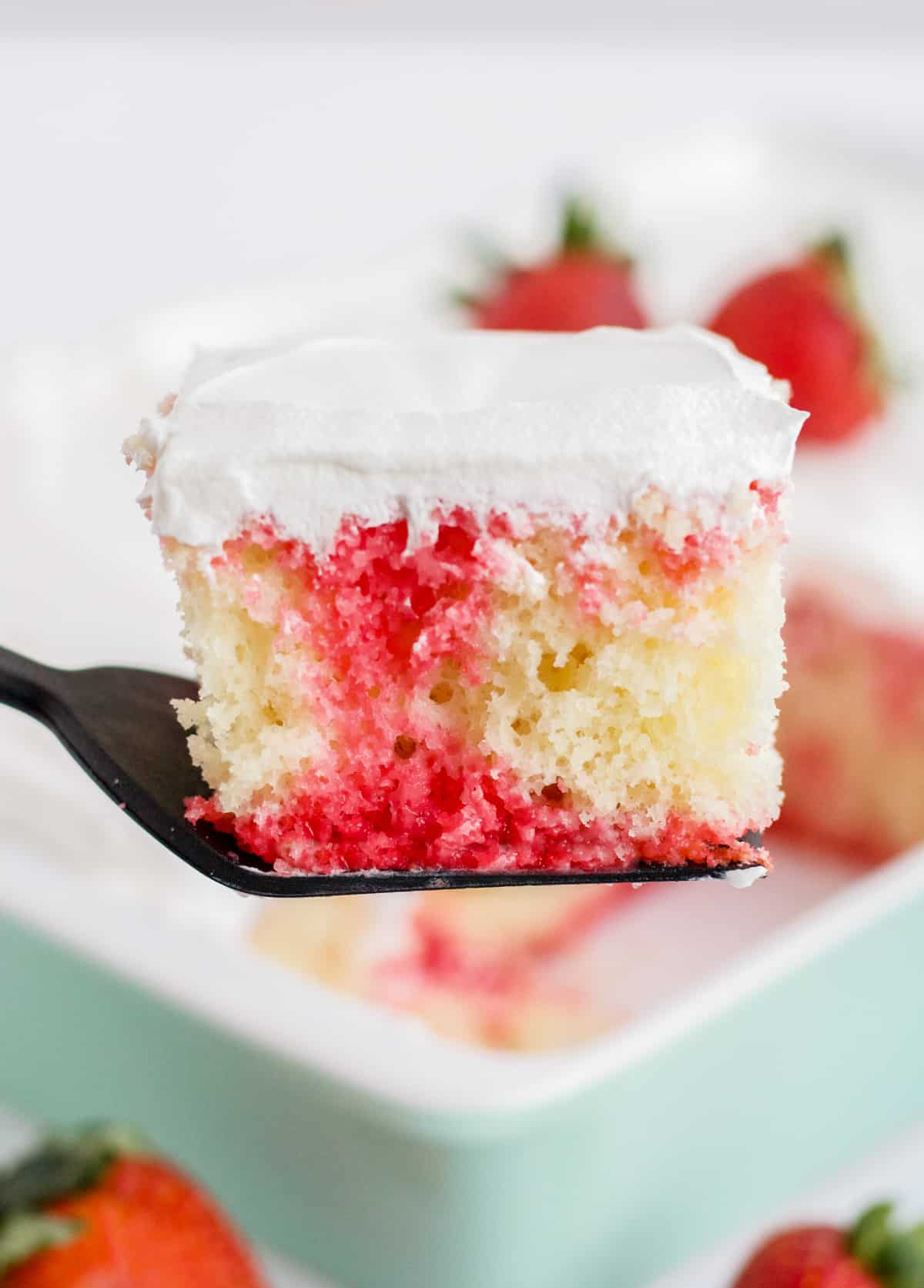 Slice of Poke Cake being held up by cake server showing strawberry jello