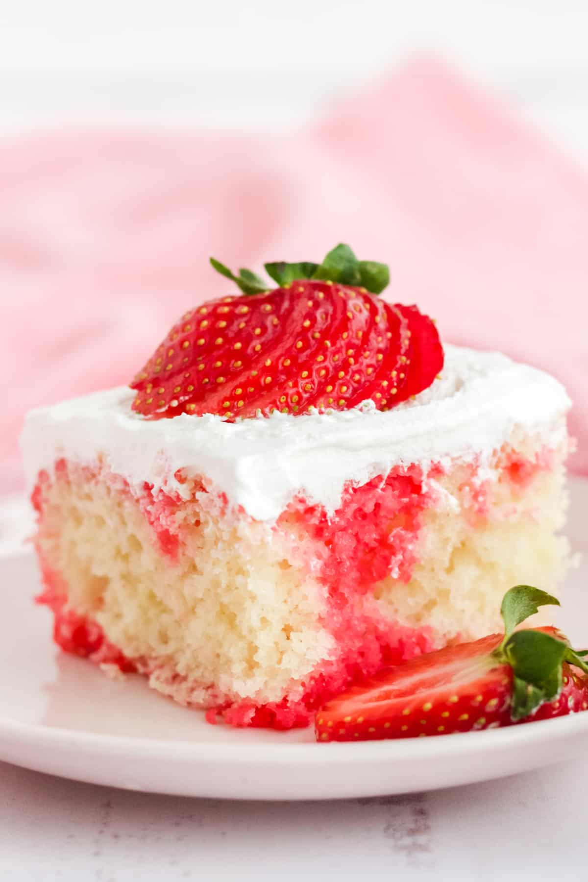 Close up of cake on white plate topped with fanned strawberry