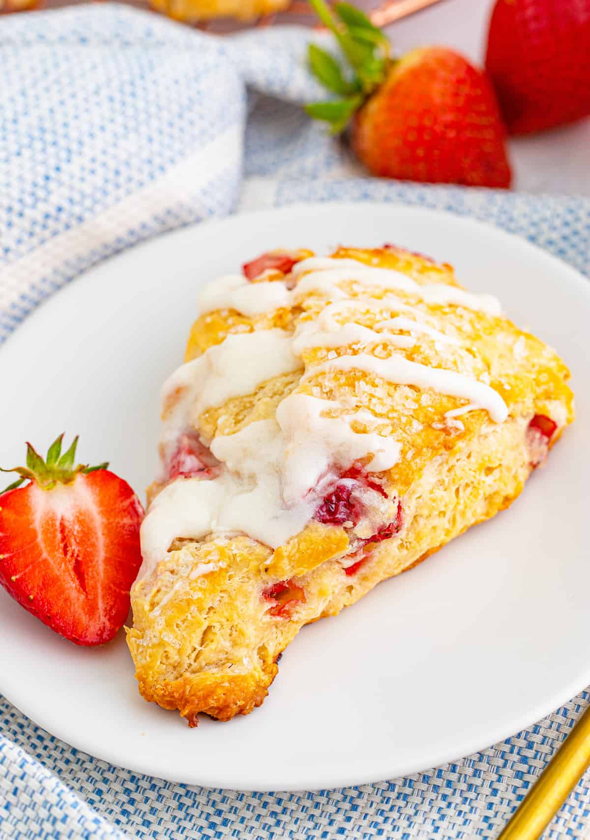One Strawberry Scone on white plate with half a strawberry