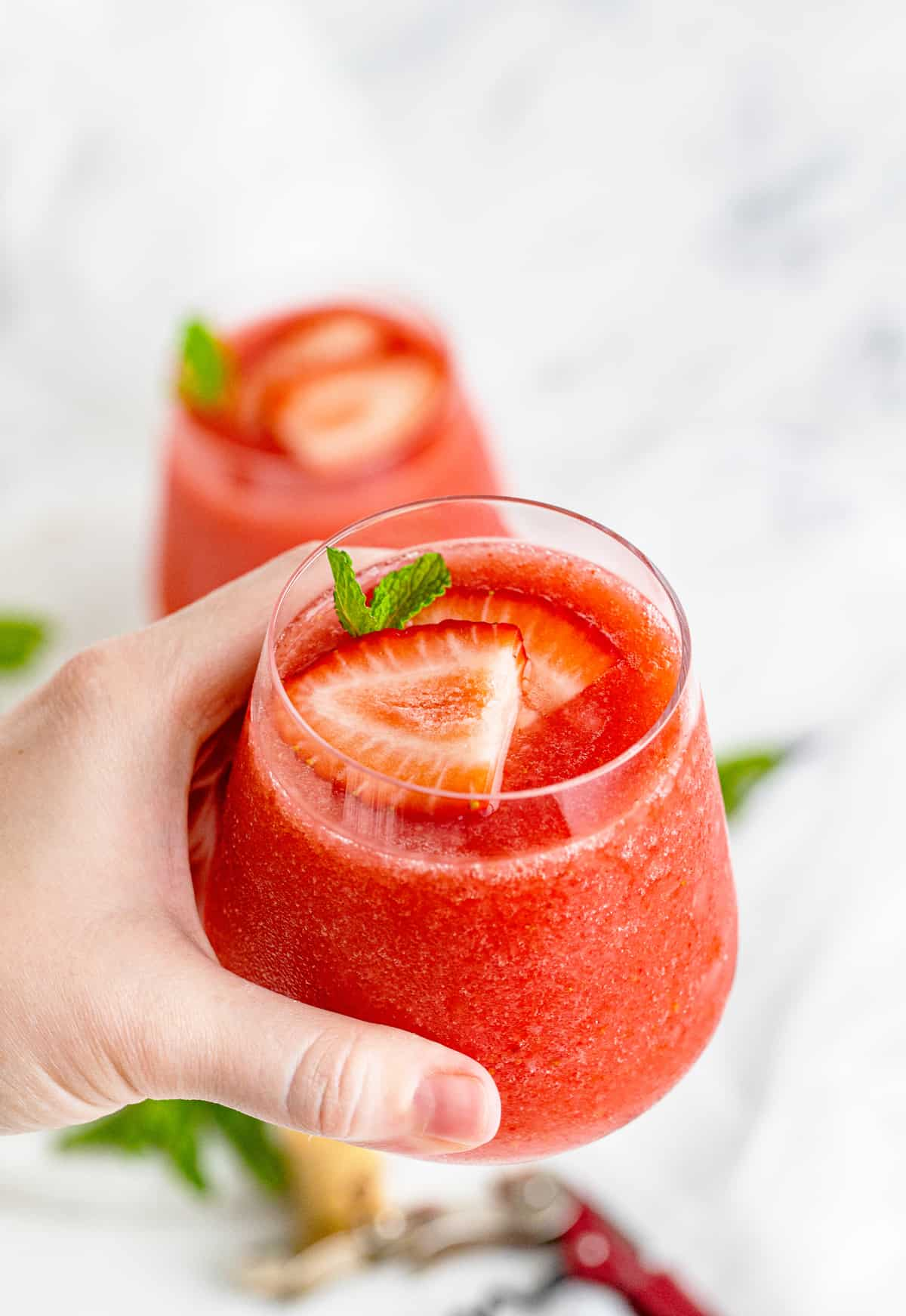 Hand holding up one glass of the Strawberry Wine Slushies showing the strawberries and mint