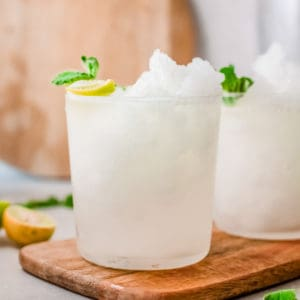 Square close up image of drink in glass with lime and mint