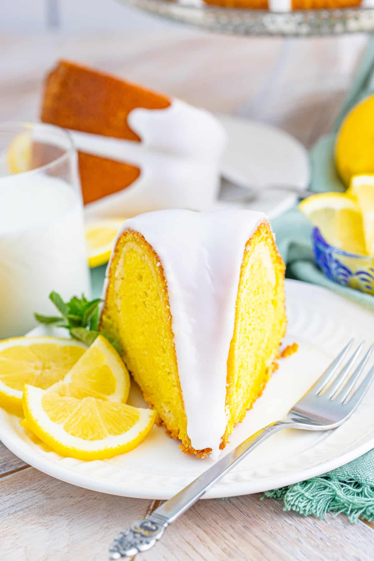 Front facing slice of cake on white plate with fork and lemons